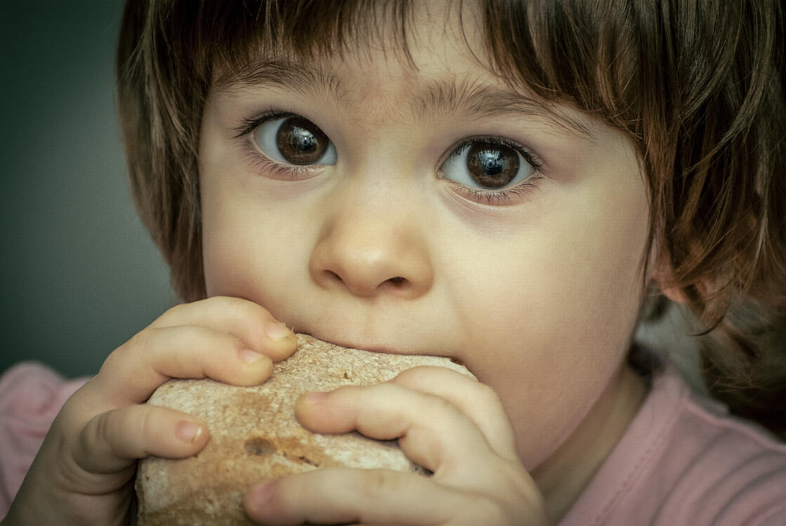 Hungry Child Eating Bread
